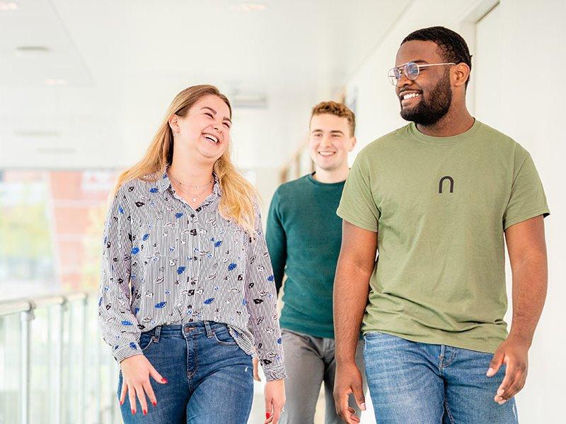 Voltijd studenten lopen lachend op gang Almere