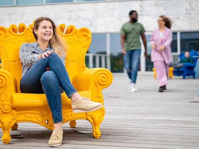 Voltijd student lachend en zittend in fauteuil Almere