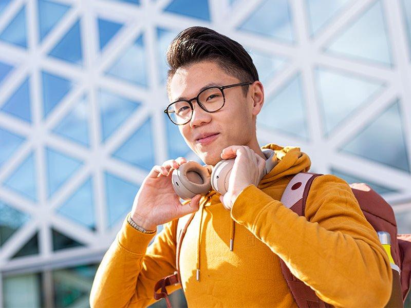 Voltijd student met koptelefoon voor X-gebouw Zwolle
