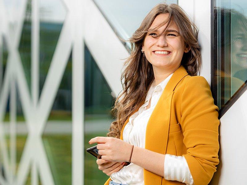 Lachende voltijd student leunend tegen X-gebouw Zwolle
