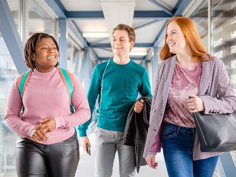 Voltijd studenten lachen en lopen over loopbrug Zwolle