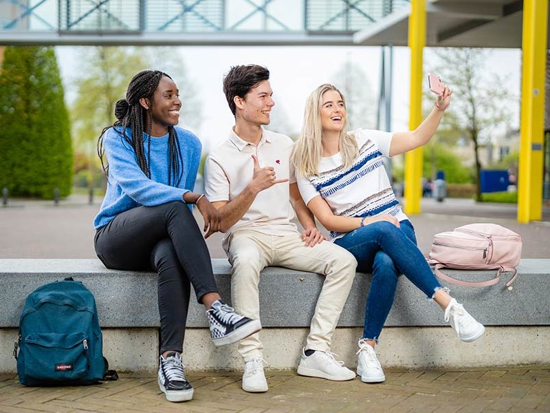 Groepje voltijd student lachen en maken selfie buiten Zwolle